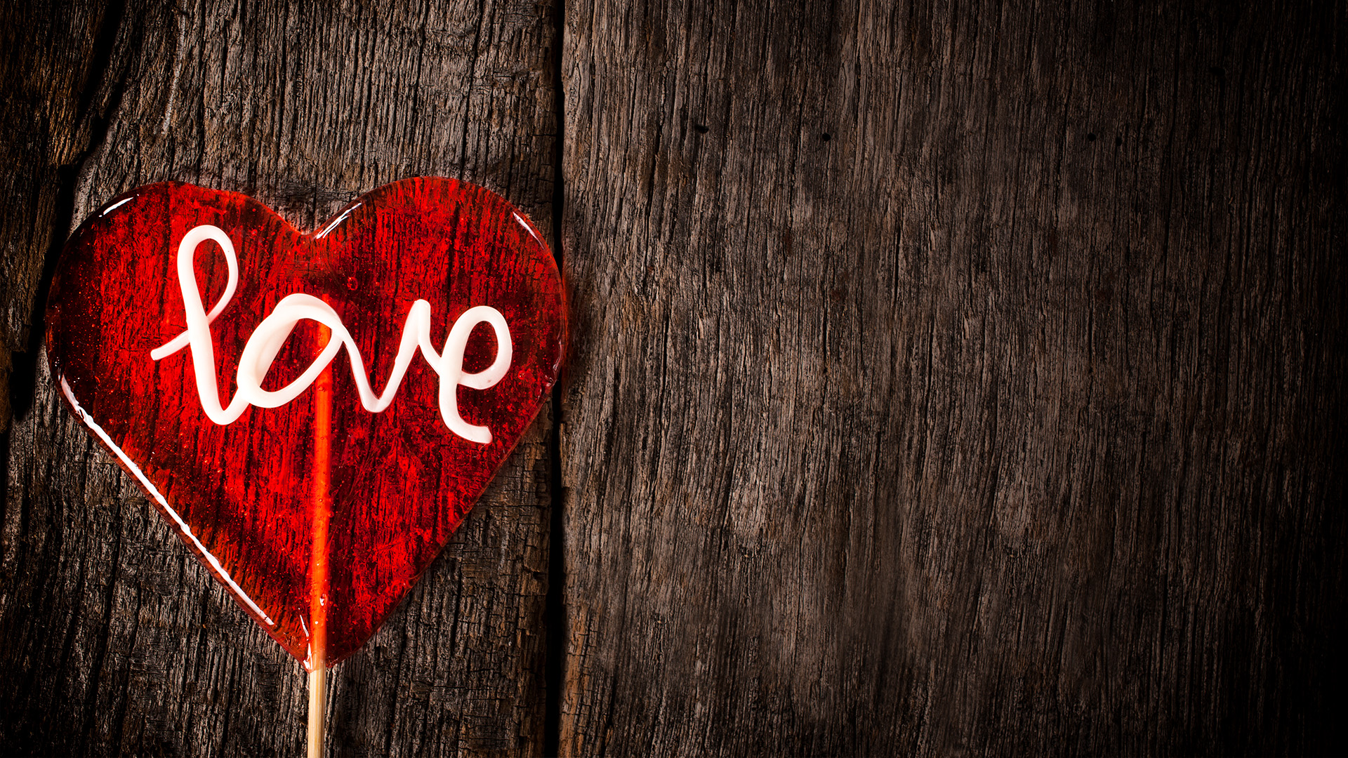 Love Lollipop On Dark Old Wooden Background